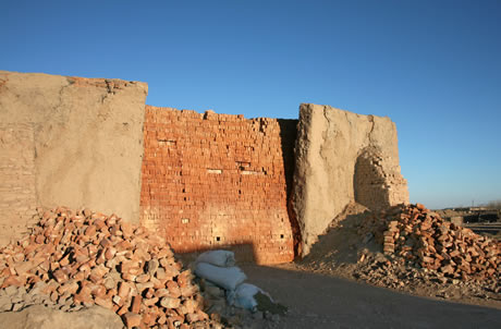 Here is a packed brick kiln. The red colour means that these bricks have been fired. The clay walls of the kiln, buttressed by bricks, are used and re-used