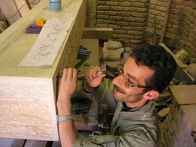 Here, the ustad (master craftsman) is adding more small pieces of the 'artificial stone' to smaller defects in the memorial. Unusually, this ustad is a young man – most are much older