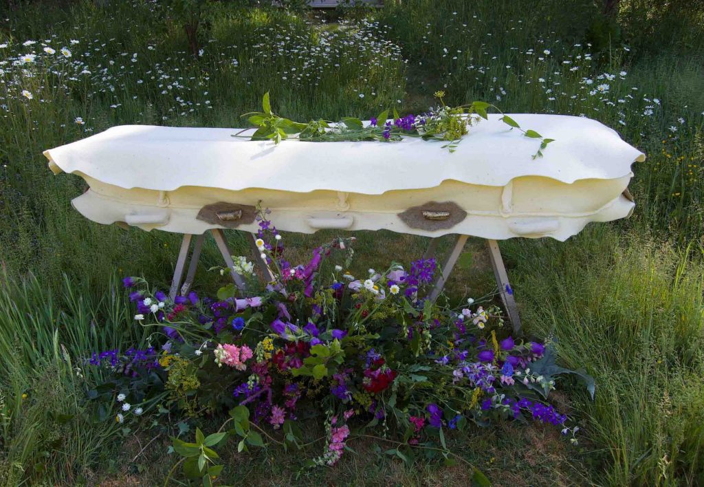 A felt cocoon -  much more gentle than a coffin. laid out in a country setting with some lovely flowers.  Contact https://bellacouche.com/