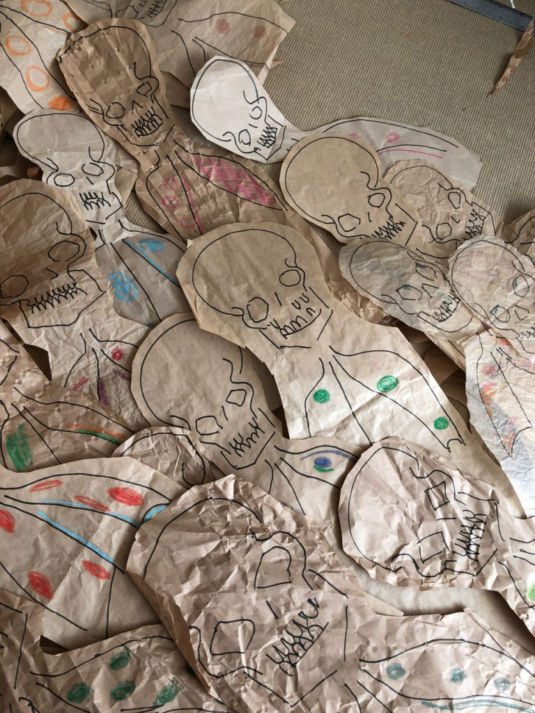 Dead bodies ankle deep on the floor. Skulls and abnormal Xrays  - drawn on recycled packsging